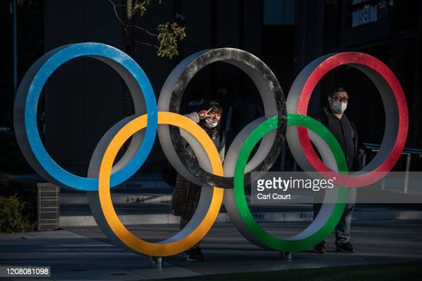People wearing face masks pose for photographs next to Olympic Rings on March 24, 2020 in Tokyo, Japan. Although an official decision is yet to be...