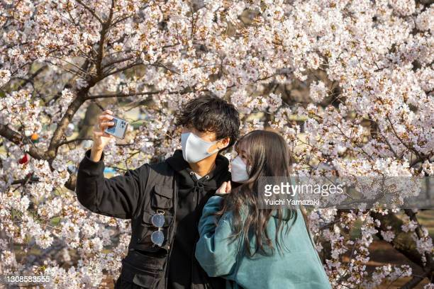People wearing face masks pose for photos during the cherry blossom bloom on March 23, 2021 in Tokyo, Japan. On March 14, the Japan Meteorological...