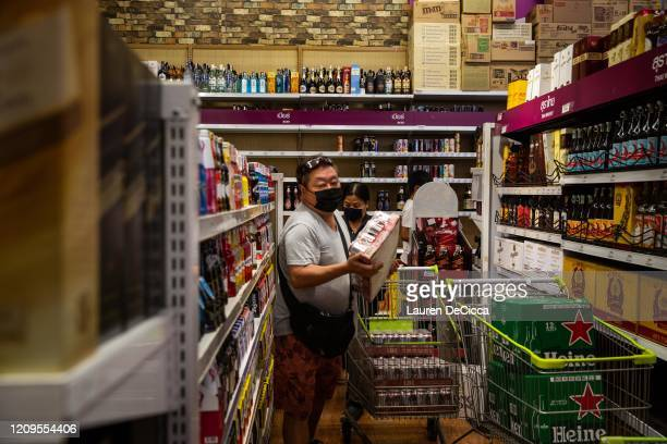 People wearing face masks purchase cases of beer at a Big C supermarket the night before a citywide alcohol ban on April 9 2020 in Bangkok Thailand...