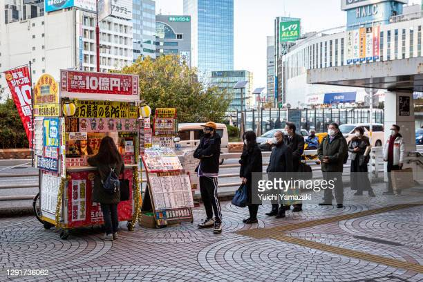 People wearing face masks queue in front of a lottery stand on December 17, 2020 in Tokyo, Japan. Tokyo confirmed a record high of 822 new cases of...