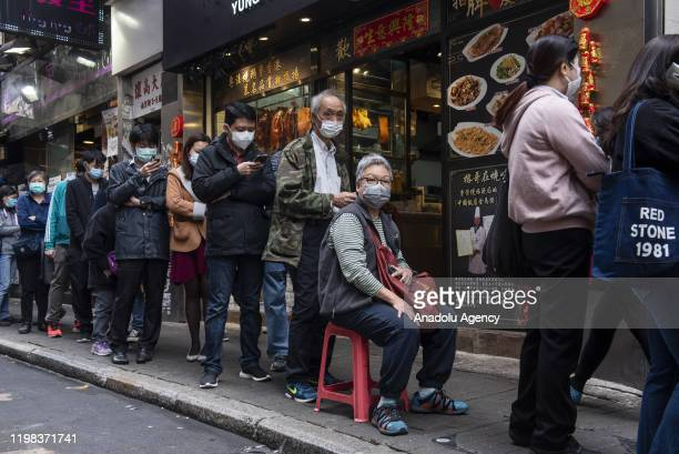 People wearing face masks queue in line for several hours at a cosmetic store to buy sanitary masks in fear of coronavirus outbreak and stock...