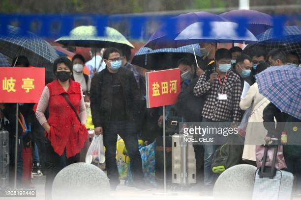 People wearing face masks queue up outside to buy tickets at the railway station in Macheng, in Chinas central Hubei province on March 25, 2020. -...