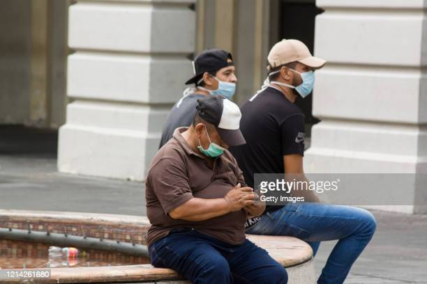 People wearing face masks rest on a public space on May 20, 2020 in Guayaquil, Ecuador. After 63 days of strict lockdown to curb spread of COVID-19,...