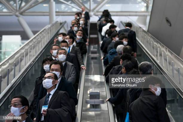 People wearing face masks ride escalators on February 13, 2020 in Tokyo, Japan. At least 219 passengers and crew onboard the Diamond Princess cruise...
