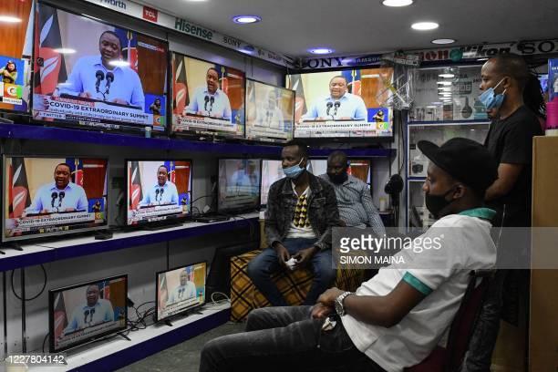 People wearing face masks sit inside an electronics shop as Kenya's President Uhuru Kenyatta is seen on television screens while giving an address to...