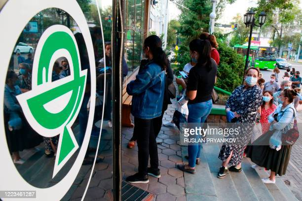 People wearing face masks stand in a line outside a pharmacy in Almaty on June 29, 2020. - Kazakhstan's president on June 29 criticised top officials...