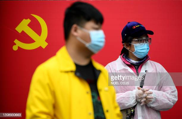 People wearing face masks stand in front of a Communist Party of China flag along a street in Wuhan, China's central Hubei province on April 2, 2020....