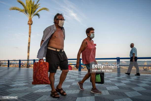 People wearing face masks to protect against the spread of coronavirus walking in El Postiguet beach of Alicante as COVID-19 cases are increasing in...