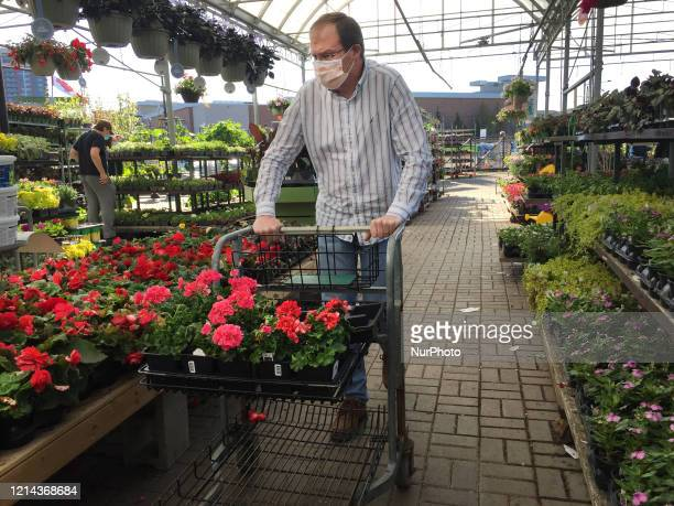 People wearing face masks to protect them from the novel coronavirus while shopping for flowers and plants at a garden centre during the Spring...