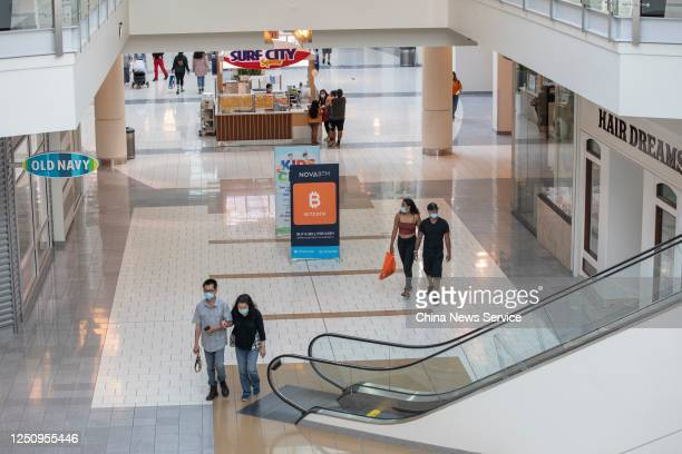 People wearing face masks visit a shopping mall amid the coronavirus outbreak on June 19, 2020 in San Mateo, California.