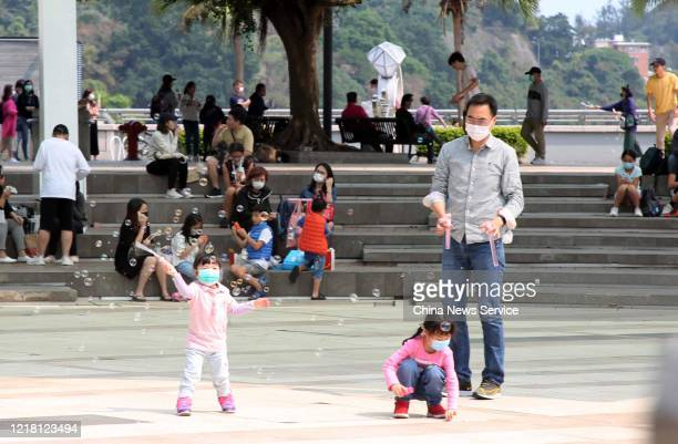People wearing face masks visit Stanley seaside village during the 3day Easter holiday amid the coronavirus outbreak on April 10 2020 in Hong Kong...