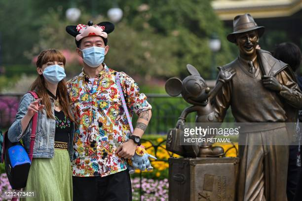 People wearing face masks visit the Disneyland amusement park in Shanghai on May 11 2020 Disneyland Shanghai reopened on May 11 to the public after...