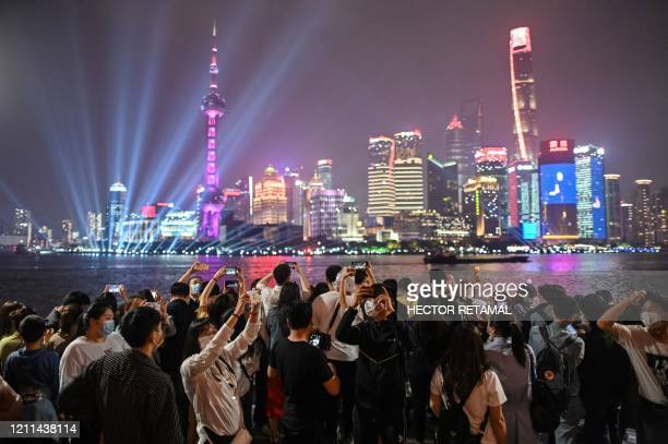 TOPSHOT People wearing face masks visit the promenade on the Bund along the Huangpu River during a holiday on May Day or International Workers' Day...