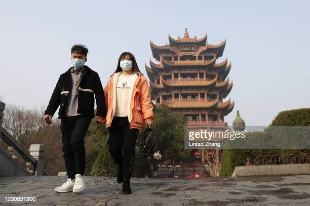 People wearing face masks visit the Yellow Crane Tower on January 28, 2021 in Wuhan, China. In order to curb the spread of the new crown pneumonia...