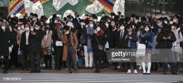People wearing face masks wait at a red light at a scramble intersection in Tokyo's Shibuya district on Dec. 16, 2020. The Tokyo metropolitan...