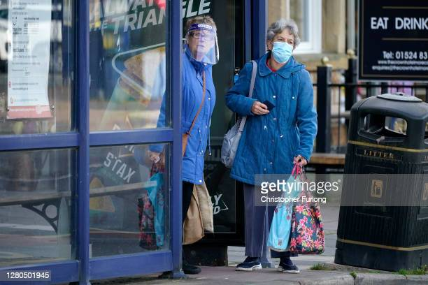 People wearing face masks wait for a bus on October 16, 2020 in Morecambe, England. The Lancashire region will go into Tier 3 of Covid-19 lockdown...