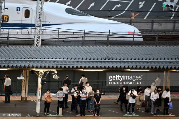 People wearing face masks wait for a train while a Shinkansen Japans high speed train passes by the Shimbashi station in Tokyo on June 10 2020
