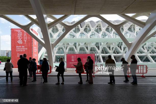 People wearing face masks wait in a queue to get vaccinated at the City of Arts and Sciences of Valencia. The good rate of vaccination in the...