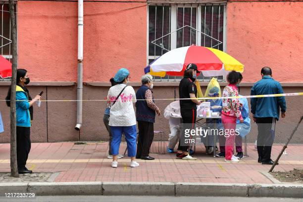 People wearing face masks wait in line to be tested for the COVID19 coronavirus on a street in Mudanjiang Chinas northeastern Heilongjiang province...
