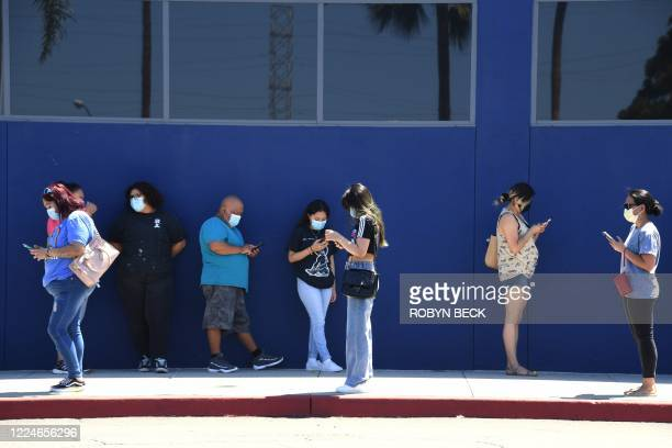 People wearing face masks wait in line to shop at Ikea in Carson California on July 4 2020 the US Independence Day holiday