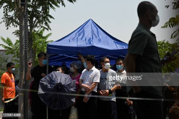 People wearing face masks wait to take a swab test for the COVID-19 coronavirus at a testing site in Beijing on June 18, 2020. - Beijing reported...