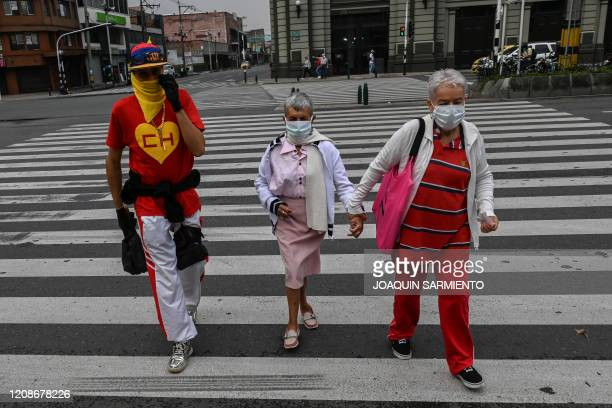 People wearing face masks walk across a zebra crossing in Medellin on March 30 2020 as Colombia holds a mandatory preventive isolation to slow the...