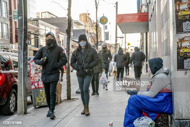 People wearing face masks walk along Queen street. Toronto is now under new lockdown orders as it struggles to contain a new wave of coronavirus.