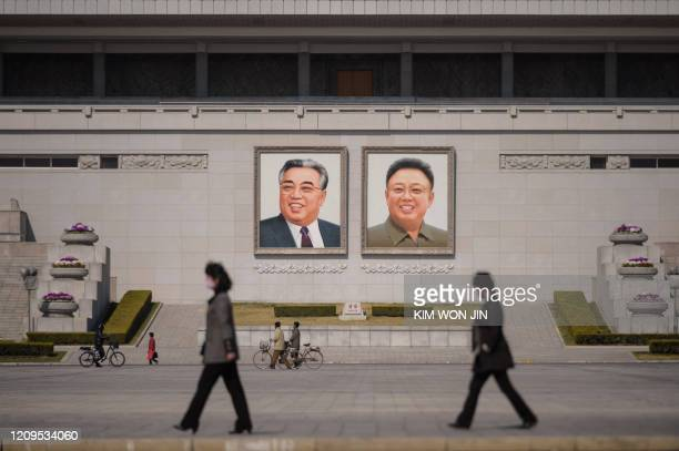 People wearing face masks walk before the portraits of late North Korean leaders Kim Il Sung and Kim Jong Il on Kim Il Sung Square in Pyongyang on...