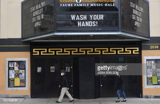 People wearing face masks walk by a closed theatre with a message about staying healthy in Berkeley California on March 18 2020 San Francisco along...