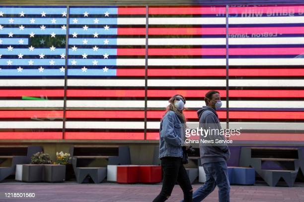 People wearing face masks walk by a light box of American flag at Times Square on April 12 2020 in New York City