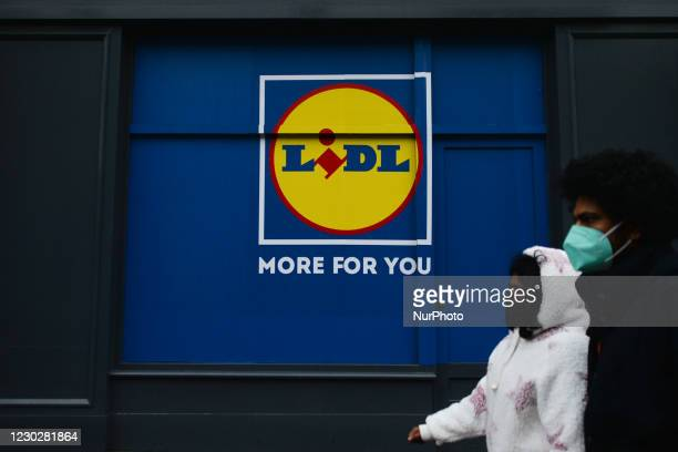 People wearing face masks walk by a logo of LIDL in Dublin's city centre. On Wednesday, December 23 in Dublin, Ireland.