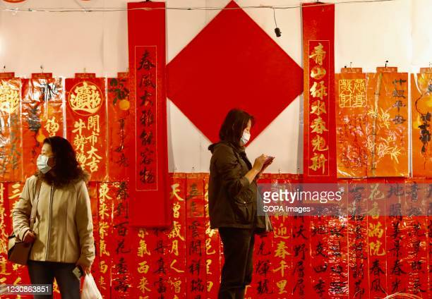 People wearing face masks walk by a wall filled with blessing ornaments ahead of the Lunar New Year celebration at a night market street. Prominent...