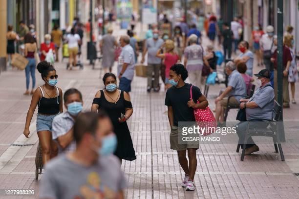 People wearing face masks walk down a shopping street in the Las Delicias neighbourhood of Zaragoza in northeastern Spain on August 10, 2020. - Spain...