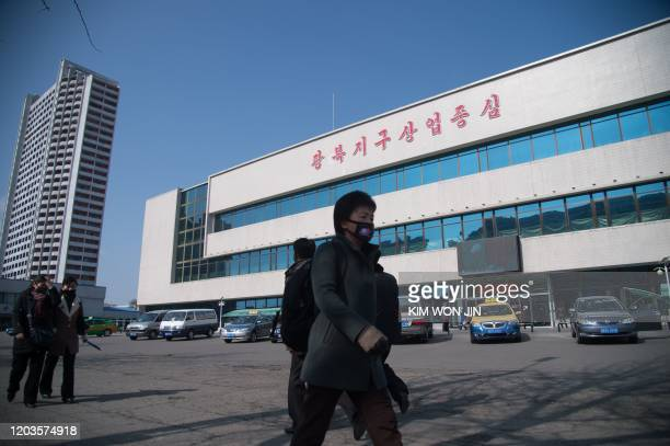 People wearing face masks walk down Kwangbok street in Pyongyang on February 26 2020 The novel coronavirus has killed over 2700 people and infected...