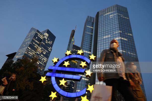 People wearing face masks walk in front of a euro sign and the former ECB headquarter in the city center of Frankfurt am Main, western Germany, on...
