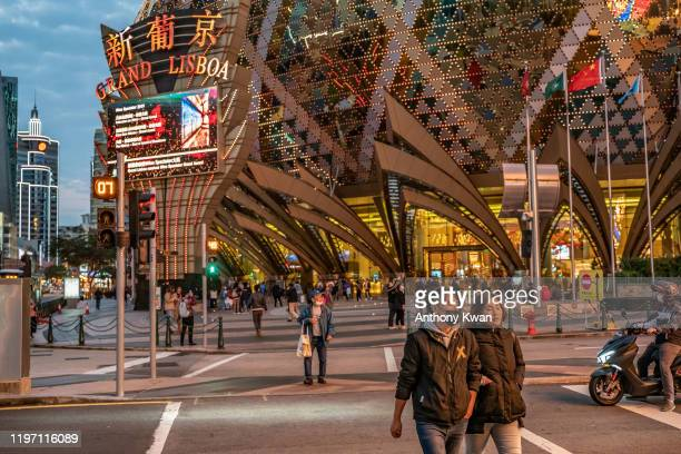 People wearing face masks walk in front of the Grand Lisboa Hotel on January 28, 2020 in Macau, China. The number of cases of a deadly new...