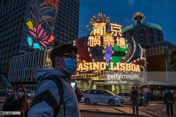 People wearing face masks walk in front of the Grand Lisboa Hotel on January 28 2020 in Macau China The number of cases of a deadly new coronavirus...