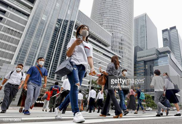 People wearing face masks walk in Nagoya, central Japan, on July 28, 2020. Aichi Prefecture reported the same day a record 110 new cases of the novel...