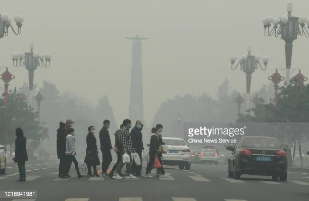People wearing face masks walk in smog on April 15, 2020 in Changchun, Jilin Province of China.