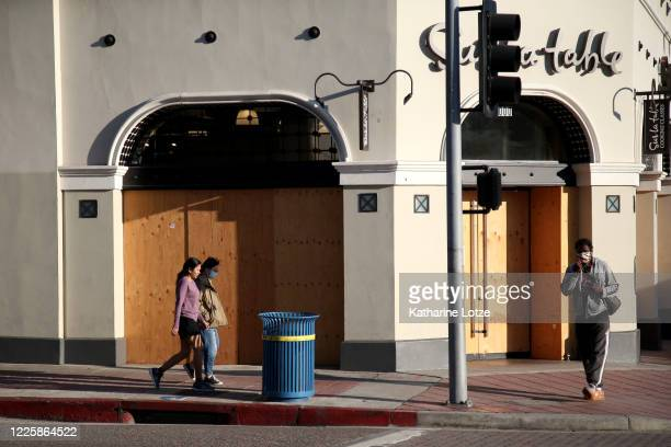 People wearing face masks walk near a closed business on May 11 2020 in Westwood California The United States has reported more than 15 million cases...