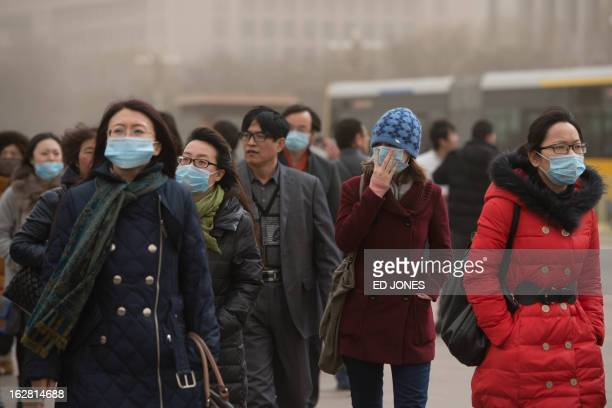 People wearing face masks walk near the Forbidden City during heavy pollution in Beijing on February 28 2013 Beijing residents were urged to stay...