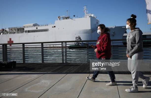 People wearing face masks walk near the USNS Mercy Navy hospital ship after it arrived in the Port of Los Angeles to assist with the coronavirus...