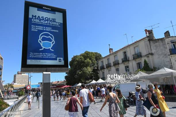 """People wearing face masks walk next to a billboard reading: """"Mandatory mask in downtown Montpellier"""", on August 14 in Montpellier, southern France. -..."""