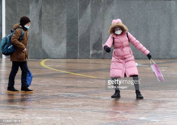People wearing face masks walk on a snow covered sidewalk after a heavy rainfall. Kiev was paralyzed, due to worsening weather conditions after...