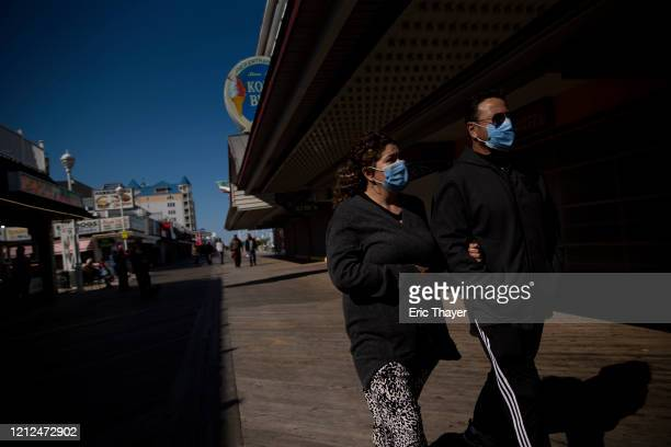 People wearing face masks walk on the boardwalk on May 10 2020 in Ocean City Maryland A popular summer tourist destination Ocean city reopened the...
