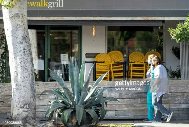 People wearing face masks walk past a closed restaurant amid Coronavirus pandemic and the Stay-At-Home regulation underway in Los Angeles, California...