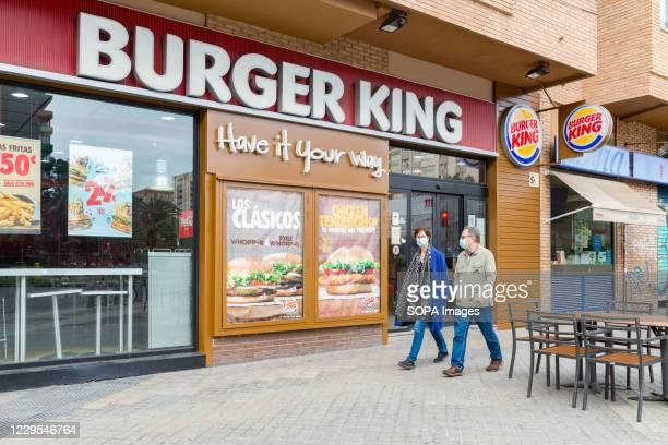 People wearing face masks walk past a fast food restaurant Burger King.