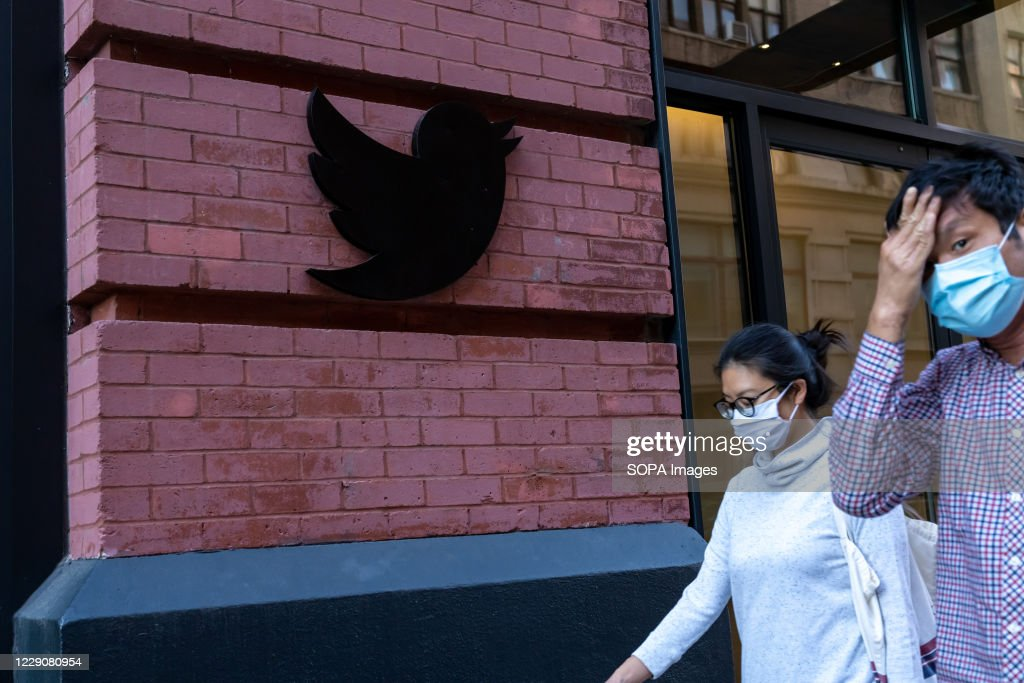 People wearing face masks walk past a Twitter logo outside... : News Photo
