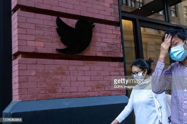 People wearing face masks walk past a Twitter logo outside their New York City headquarters. Facebook and Twitter took steps to limit the spread of a...