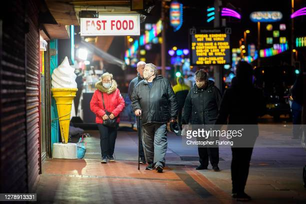People wearing face masks walk past fast food stalls on October 06, 2020 in Blackpool, England. This year to help boost the tourism trade, which has...
